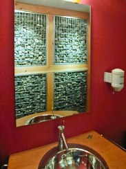 Powder room reflection showing rock rubble wall separating powder from wine cellar